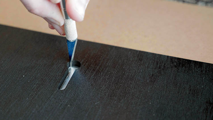 Using an X-ACTO knife to cut the foil tape away from a keyhole slot.